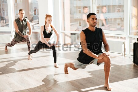 Multiethnic group of people stretching legs and doing yoga Stock photo © deandrobot