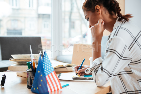 Side view of Young African Woman in library Stock photo © deandrobot