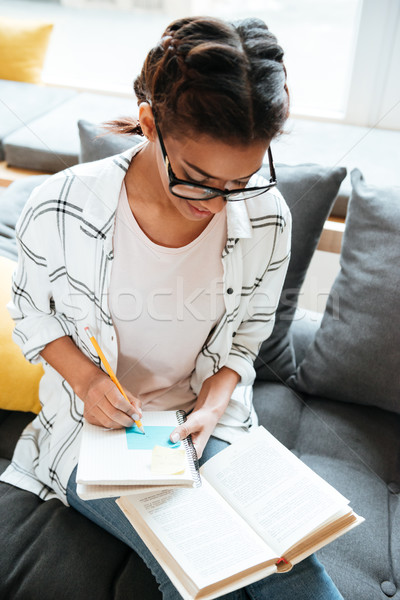 Young amazing african lady wearing glasses sitting in library Stock photo © deandrobot