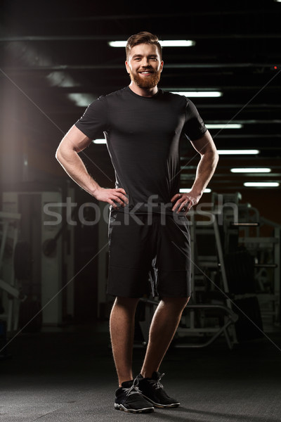 Cheerful sports man standing and posing in gym Stock photo © deandrobot