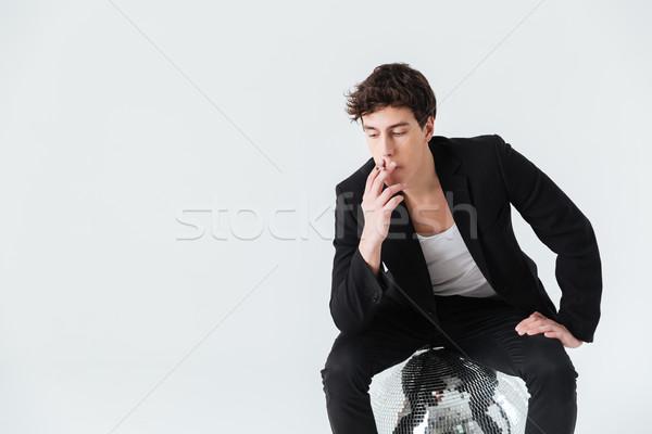 Uomo seduta disco ball fumare sigaretta suit Foto d'archivio © deandrobot