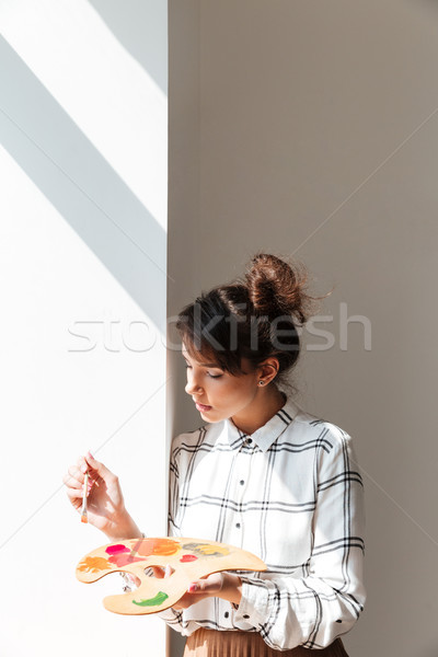 Woman artist holding palette while standing in studio Stock photo © deandrobot