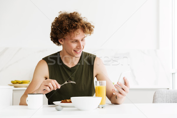 Cheerful man using mobile phone and eating pastries Stock photo © deandrobot