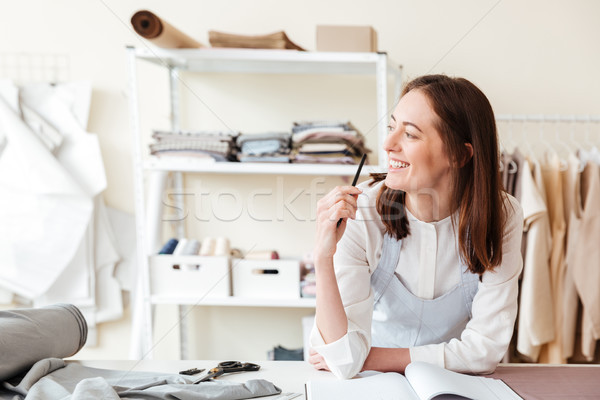 Smiling woman seamstress with pencil looking aside Stock photo © deandrobot