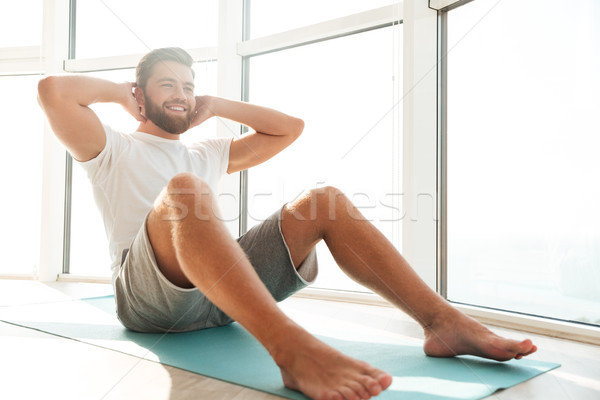 Smiling Handsome bearded man doing abdominals exercises near the window Stock photo © deandrobot