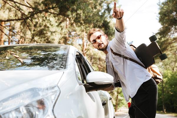 Przystojny mężczyzna deskorolka odkryty stałego samochodu wskazując Zdjęcia stock © deandrobot