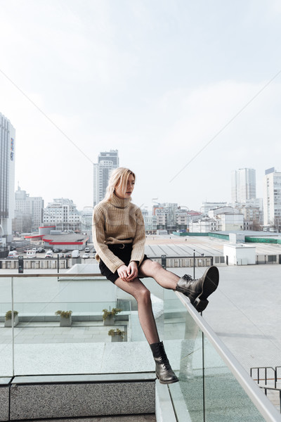 Concentrated young blonde lady outdoors. Looking aside. Stock photo © deandrobot
