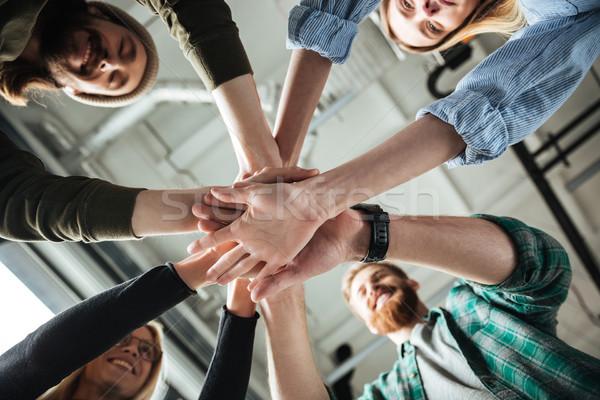 Colleagues in office holding hands of each other Stock photo © deandrobot