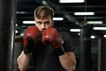 Sportsman holding punching bag on his shoulder in gym Stock photo © deandrobot