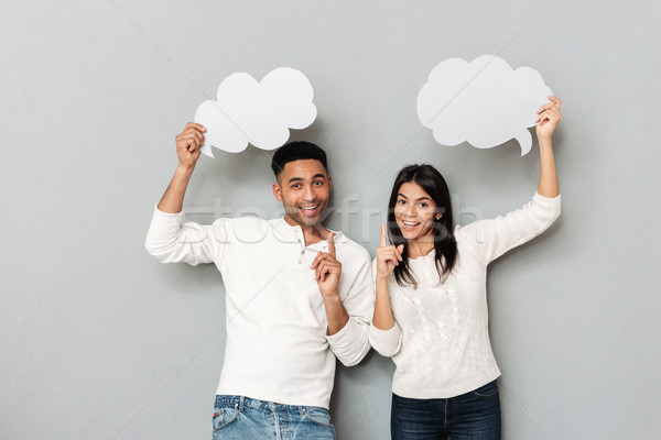 Cheerful couple pointing their fingers up and holding bubbles Stock photo © deandrobot
