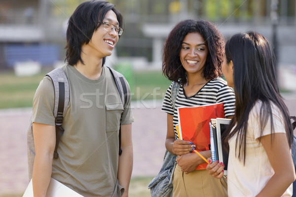 Multiethnic group of young smiling students standing and talking Stock photo © deandrobot