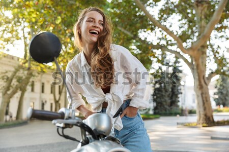Happy african woman rides on modern motorbike in park Stock photo © deandrobot