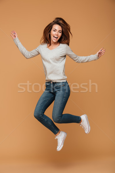 Full length photo of charming young woman in casual wear jumping Stock photo © deandrobot