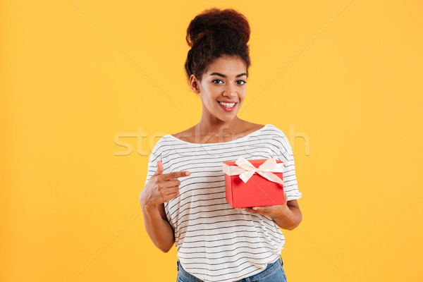 Happy african lady looking camera and pointing with finger at present Stock photo © deandrobot