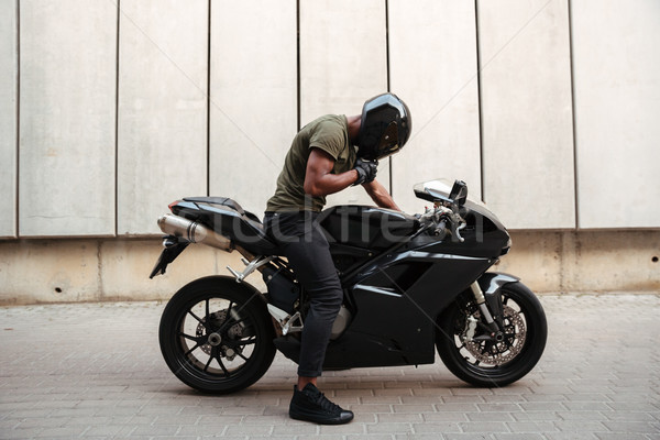 Portrait of an afro american man taking off a helmet Stock photo © deandrobot