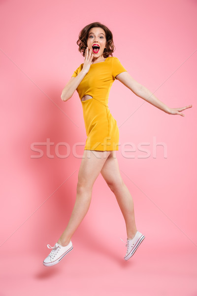 Full length portrait of happy exited woman in elegant yellow dre Stock photo © deandrobot