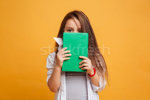 Scared little girl child covering face with book. Stock photo © deandrobot
