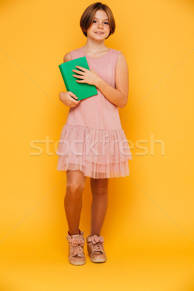 Full-length shot of smiling girl holding green book isolated Stock photo © deandrobot