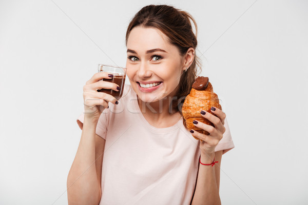 Portrait of a satisfied pretty girl eating croissant Stock photo © deandrobot