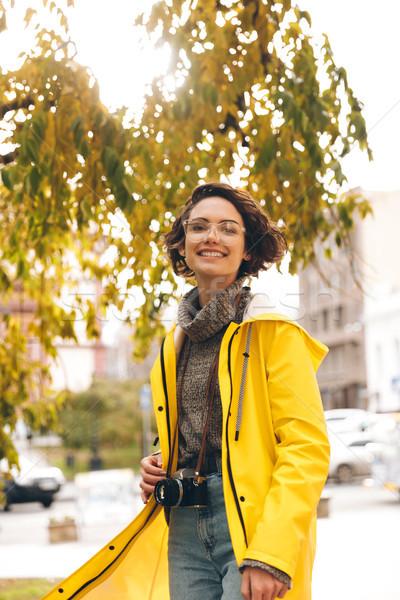 Derűs fiatal hölgy fotós kép esőkabát Stock fotó © deandrobot