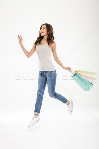 Full-length image of ecstatic adult female levitating or jumping Stock photo © deandrobot