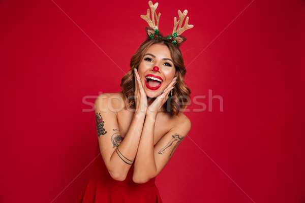 Portrait of a cheerful young girl wearing christmas deer costume Stock photo © deandrobot