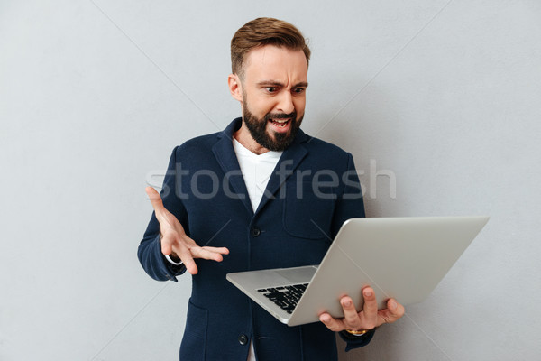 Frown serious man in suit using laptop isolated Stock photo © deandrobot