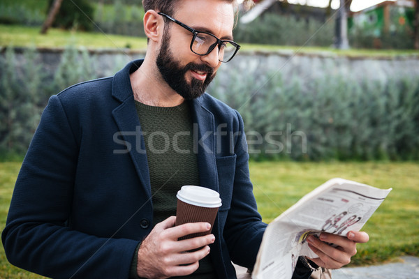 Attractive young bearded man sitting outdoors reading newspaper Stock photo © deandrobot