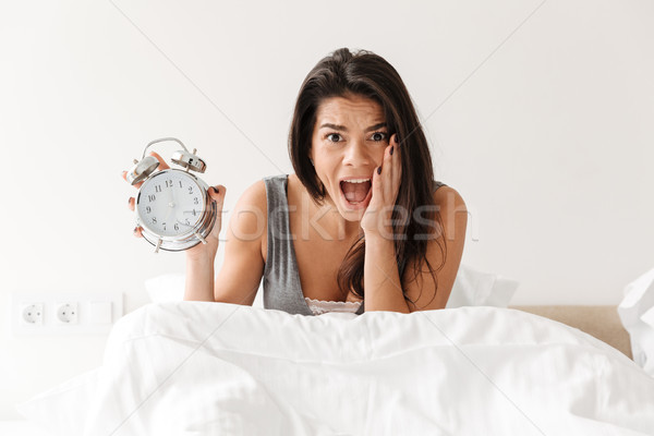 Image of shocked woman waking up and being late, holding ringing Stock photo © deandrobot