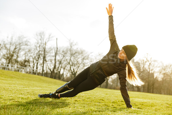 Image of sporty handicapped woman in black tracksuit, exercising Stock photo © deandrobot