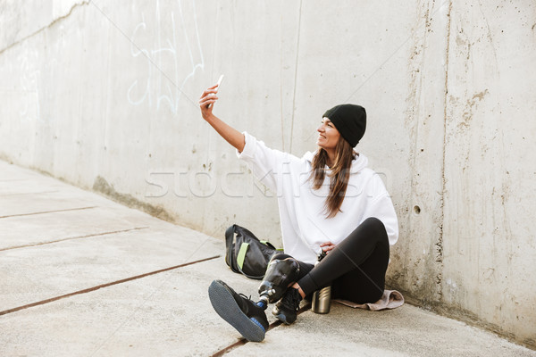Photo of modern young handicapped woman in streetwear having bio Stock photo © deandrobot