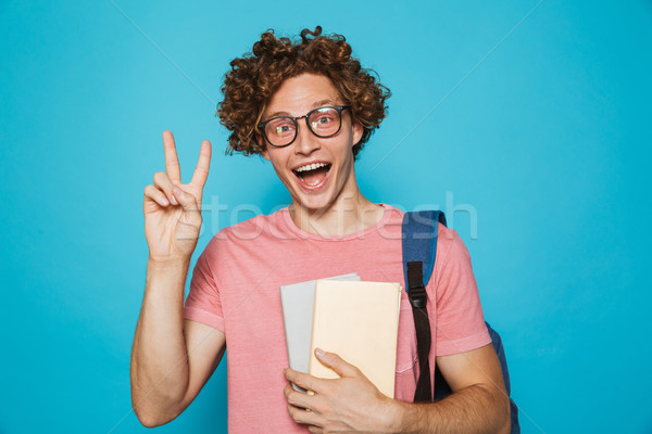 Portrait of young hipster guy with curly hair wearing glasses an Stock photo © deandrobot