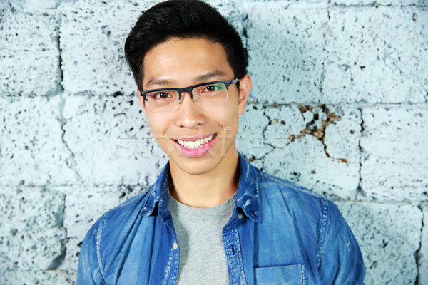 Portrait of a smiling asian man near brick wall Stock photo © deandrobot