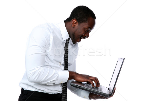 Surprised african man standing and using laptop over white background Stock photo © deandrobot