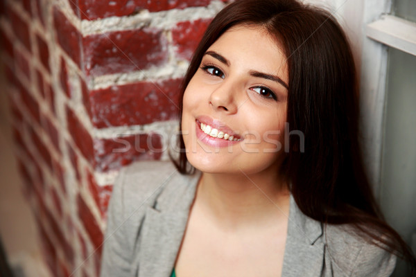 Portrait of a young smiling woman near brick wall Stock photo © deandrobot