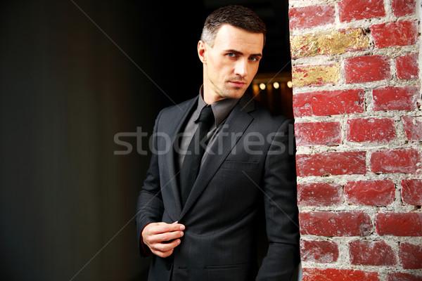 Portrait of a confident businessman standing near brick wall Stock photo © deandrobot