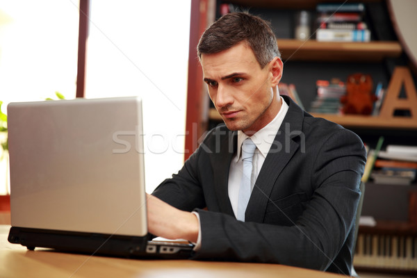 Confident businessman sitting with laptop at office Stock photo © deandrobot