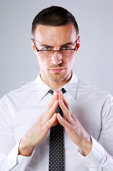 Confident businessman folding his hands together on gray background Stock photo © deandrobot