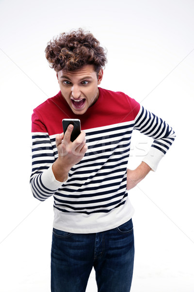Portrait of a man shouting at smartphone over gray background Stock photo © deandrobot