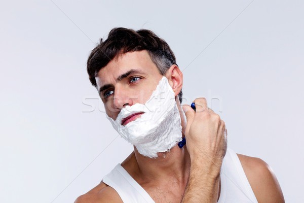 Young man shaving over gray background Stock photo © deandrobot