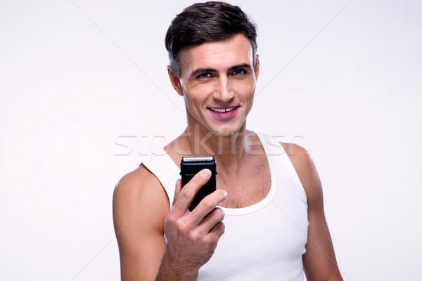 Happy man holding electric razor over gray background Stock photo © deandrobot