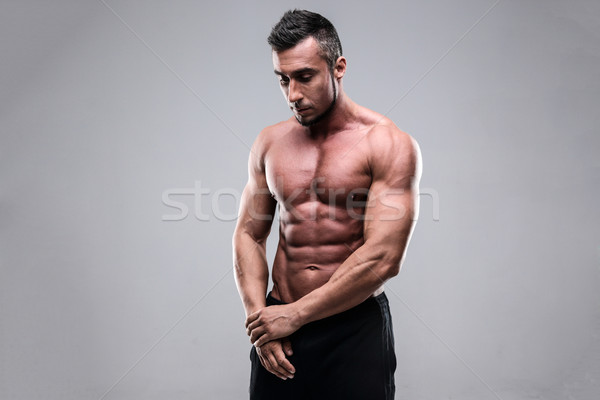 Shirtless man looking downwards over gray background Stock photo © deandrobot