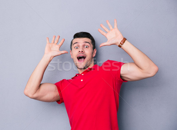 Portrait of a scared casual man  Stock photo © deandrobot