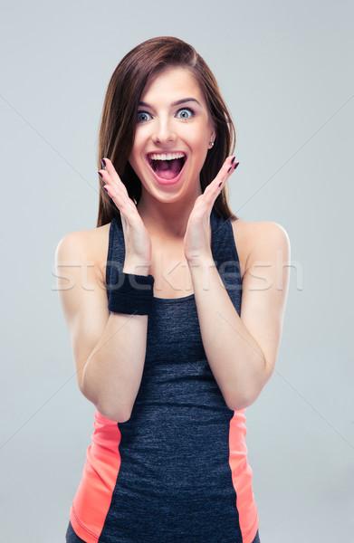 Maravilhado feliz mulher da aptidão olhando câmera cinza Foto stock © deandrobot