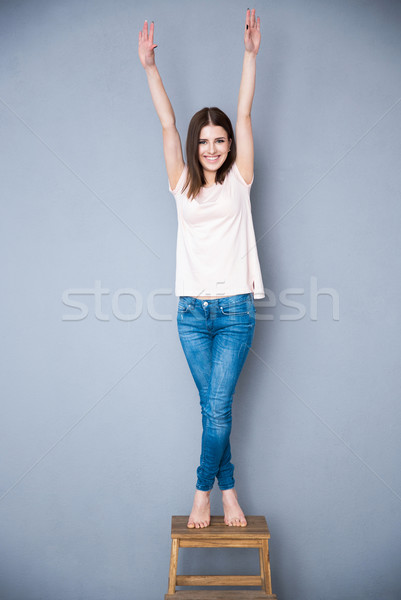 Happy young woman standing on the chair with raised hands up Stock photo © deandrobot
