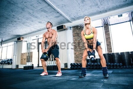 Group of a man and woman workout with kettle ball Stock photo © deandrobot