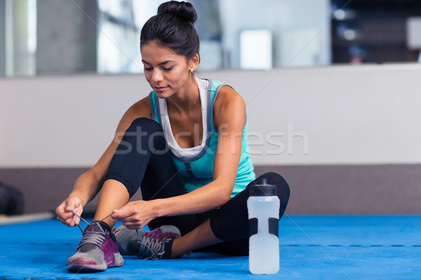 Woman tie shoelaces in gym Stock photo © deandrobot