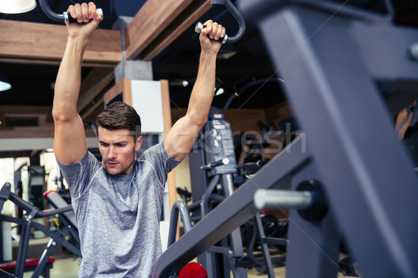 Fit man workout on fitness machine Stock photo © deandrobot