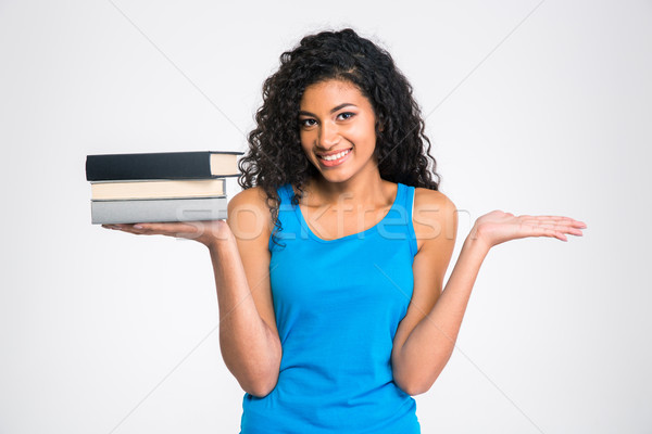 Afro american woman holding books and copyspace on the palms Stock photo © deandrobot
