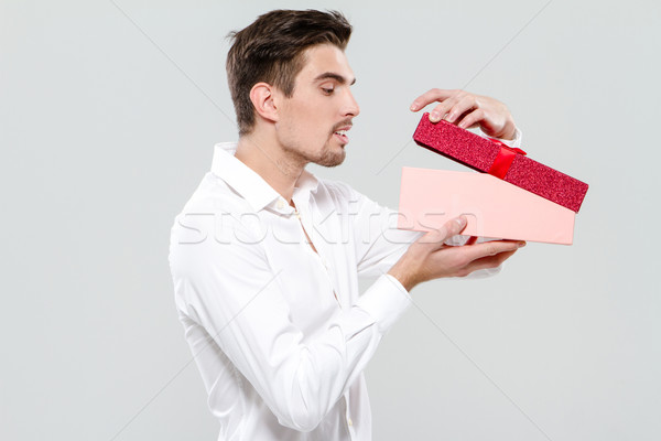Handsome man looking in pink box Stock photo © deandrobot